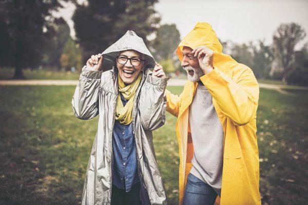 Dos jubilados con impermeables ríen mientras llueve